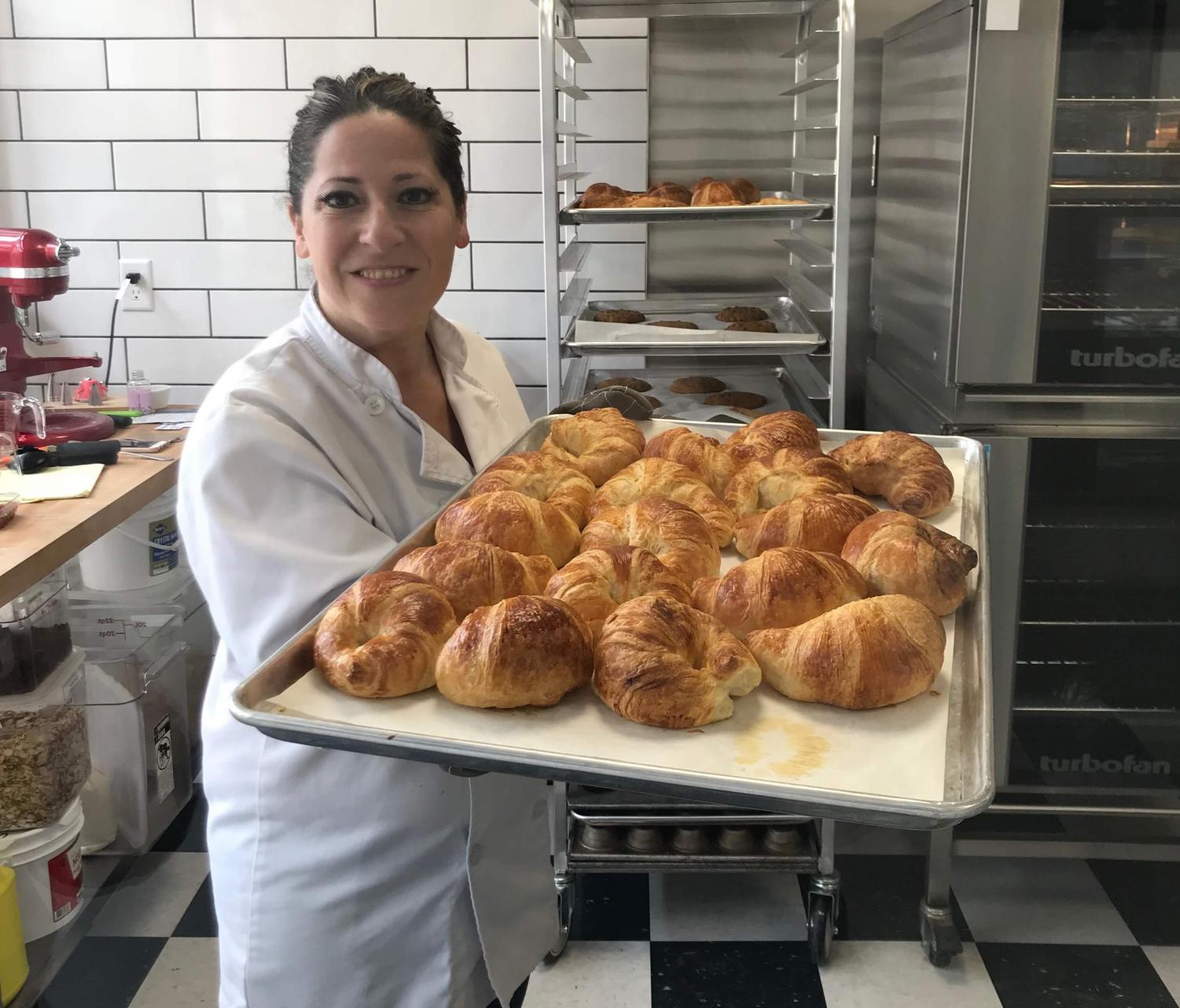 Michelle Kelly, owner and baker of Mademoiselle of Patchogue pictured with a tray of freshly baked croissants.