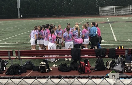 The girls huddle on the field in their Stick it to Cancer Awareness t-shirts and play for a cause Monday night at Raider Stadium.