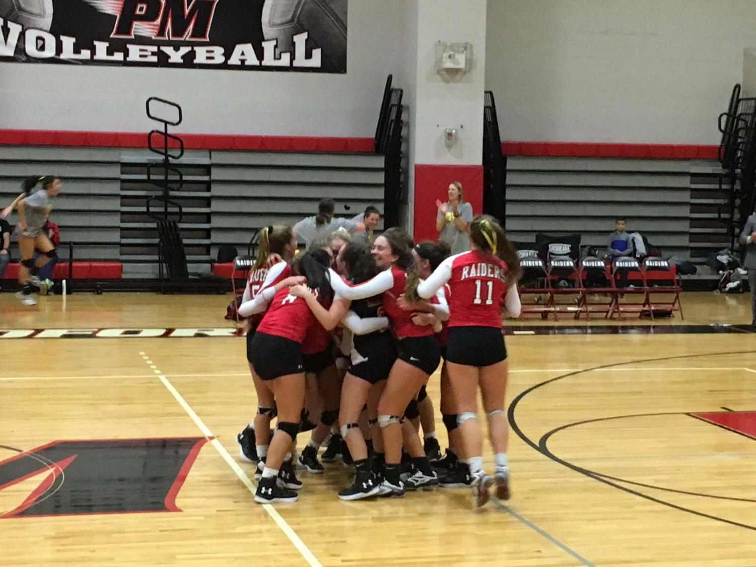 The girls' volleyball team huddle together and celebrate an amazing win over Ward Melville.