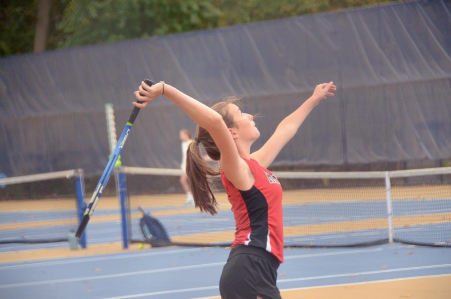 Varsity girls tennis player serves up a shot during practice this season.