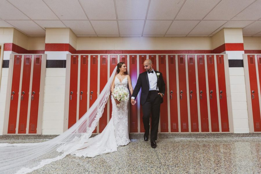 Caitlin+and+Michael+Rattien+on+their+wedding+day+this+past+summer+pictured+in+front+of+the+same+red+lockers+and+in+the+halls+of+the+high+school+where+they+first+met.+