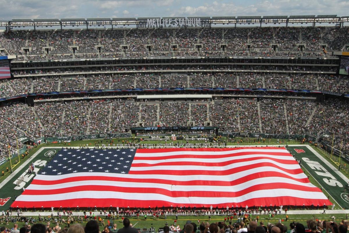 A flag is unfurled on an NFL field before start of play.